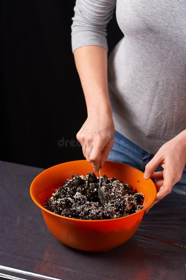 gödningsmedel och jordning som blandar i behållare arbeta i trädgården process på svart bakgrund Nära övre royaltyfria foton