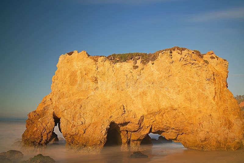 Gömda havsgrottor av kalksteninsättningar på El-matador Beach arkivfoto