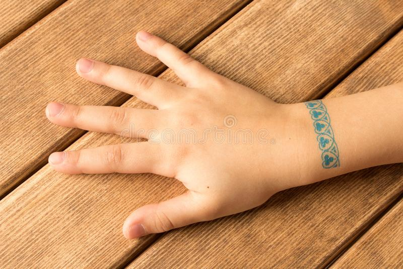 Gömma i handflatan av liten flicka med behandla som ett barn tatueringen på träbakgrund royaltyfri bild