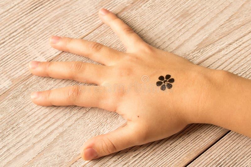 Gömma i handflatan av liten flicka med behandla som ett barn tatueringen på träbakgrund arkivbild