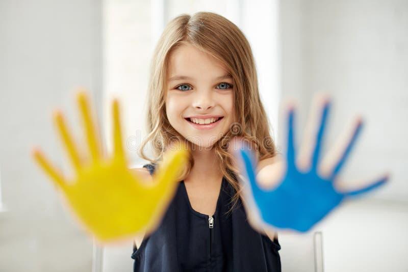 Gömma i handflatan den lyckliga målade handen för flickan visningen hemma royaltyfria foton