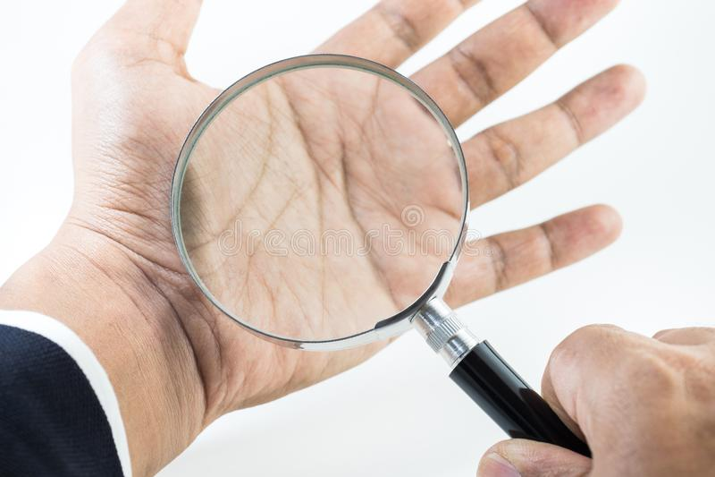 Gömma i handflatan det hållande förstoringsglaset för affärsmanhanden på royaltyfria bilder