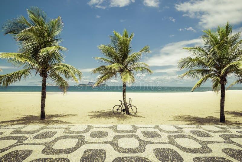 Gömma i handflatan med cykeln på den Ipanema stranden i Rio de Janeiro royaltyfri bild