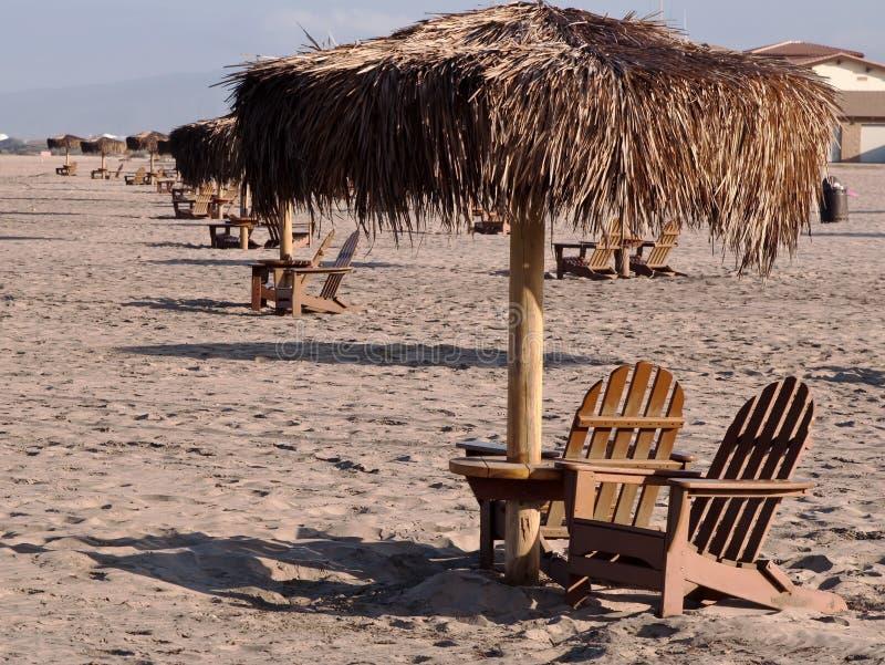 Gömma i handflatan paraplytabeller och träadiorondackstolar uppställda på en strand arkivfoto