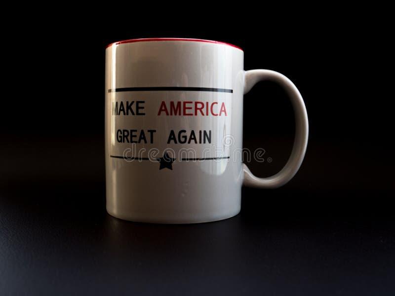 Gör Amerika den stora igen kaffekoppen i aktionen för studioljustrumf royaltyfri bild