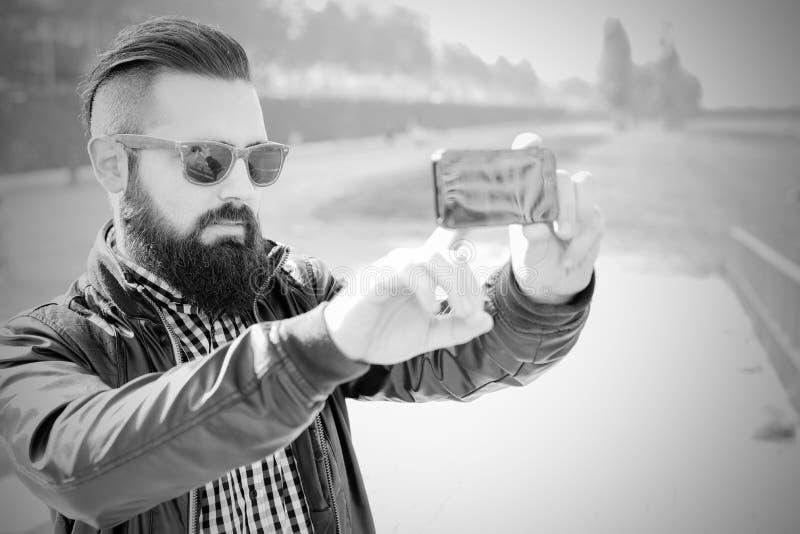 Gör den attraktiva moderna mannen för hipsteren en selfie WB arkivbild