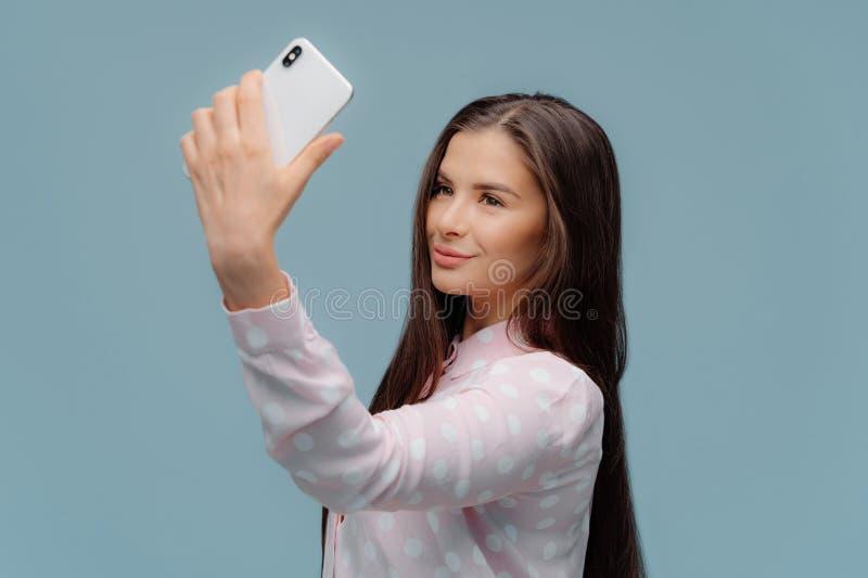 Gör den mörka synade kvinnlign för den förtjusande brunetten med att appellera blicken som in camera fokuseras av smartphonen, se arkivfoto