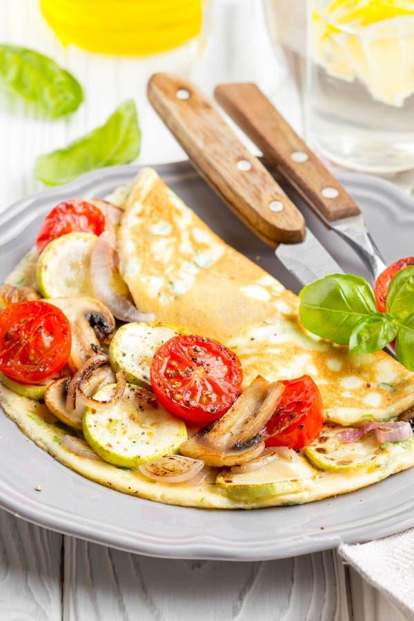 Gör den rullande omelettet med stekte grönsaker tunnare, zucchinin, tomaten, onio royaltyfri foto