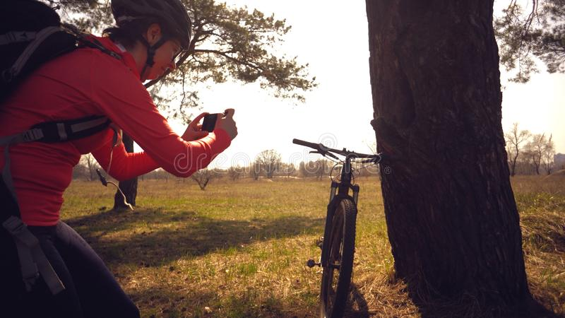Gör den turist- cyklisten för den unga caucasian kvinnaidrottsman nen fotoet på telefonen, fotografier hans cykelanseende nära tr royaltyfria bilder