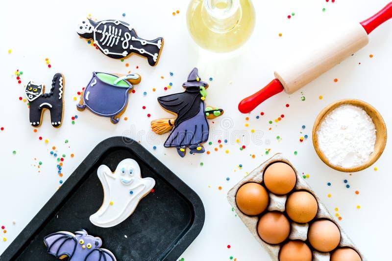 Gör det halloween pepparkakabegreppet Isläggningkakor nära kavlen, bakplåt, ägg, mjöl på den vita bakgrundsöverkanten arkivbild