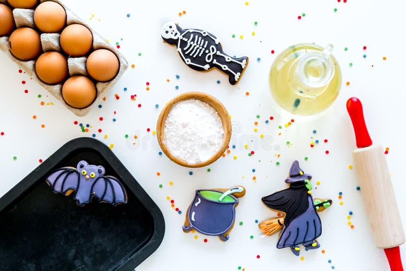 Gör det halloween pepparkakabegreppet Isläggningkakor nära kavlen, bakplåt, ägg, mjöl på den vita bakgrundsöverkanten royaltyfri bild