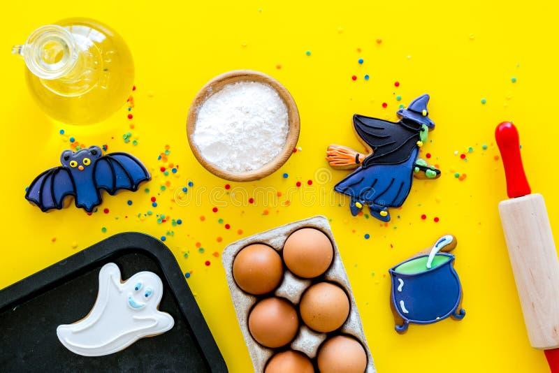 Gör det halloween pepparkakabegreppet Isläggningkakor nära kavlen, bakplåt, ägg, mjöl på gul bakgrundsöverkant arkivbilder