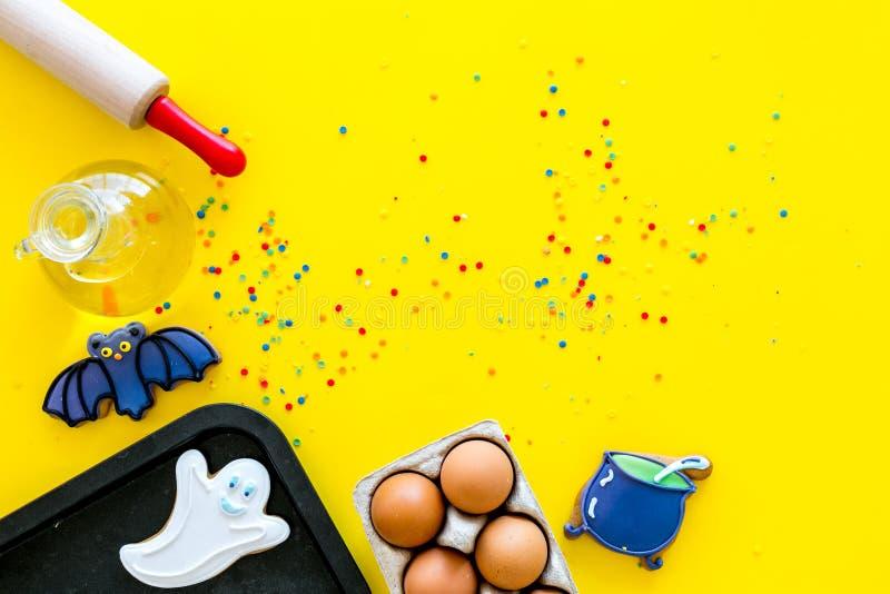 Gör det halloween pepparkakabegreppet Isläggningkakor nära kavlen, bakplåt, ägg, mjöl på gul bakgrundsöverkant royaltyfri fotografi