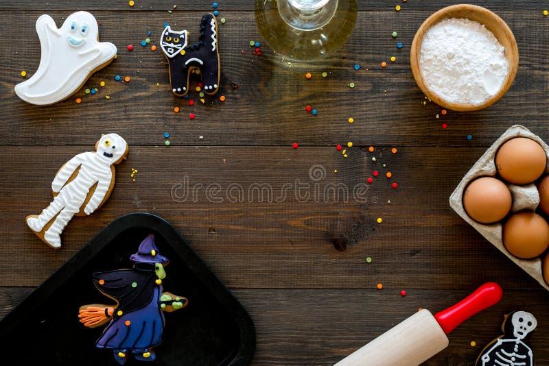 Gör det halloween pepparkakabegreppet Isläggningkakor nära kavlen, bakplåt, ägg, mjöl på mörk träbakgrund royaltyfri foto