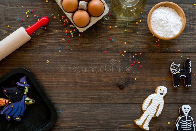 Gör det halloween pepparkakabegreppet Isläggningkakor nära kavlen, bakplåt, ägg, mjöl på mörk träbakgrund arkivfoton