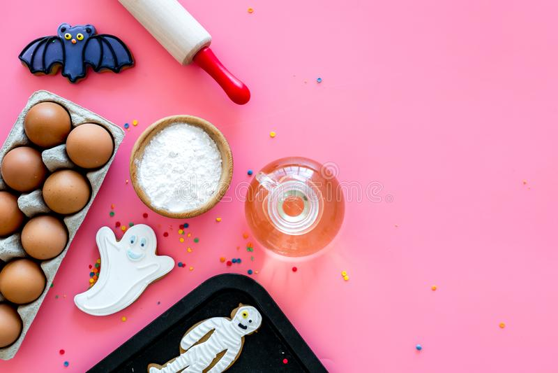 Gör det halloween pepparkakabegreppet Isläggningkakor nära kavlen, bakplåt, ägg, mjöl på rosa bakgrundsöverkant arkivfoto