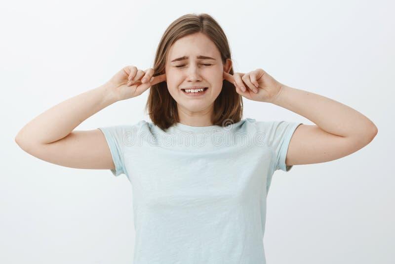 Gör detta solida stopp Den olyckliga otrygga skriande gulliga flickan med brunt hårbokslut synar och gripa hårt om tandframställn arkivbilder