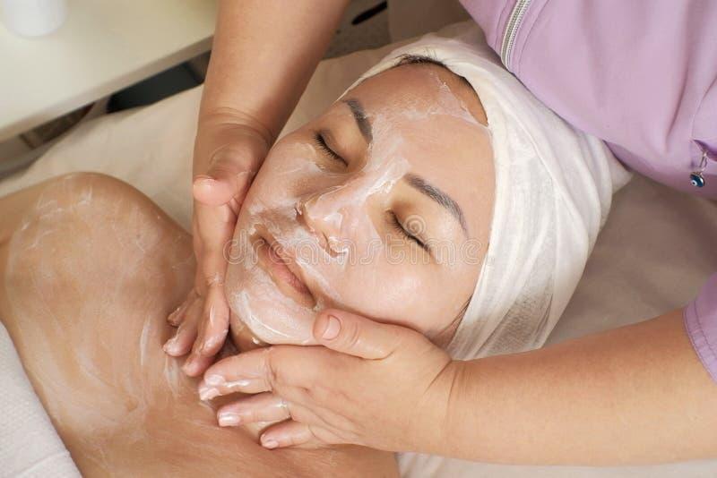 Gör en ansikts- massage för cosmetologist, en kvinna av det asiatiska utseendet Kosmetisk tillvägagångssättfaceliftkirurgi Proble royaltyfria bilder