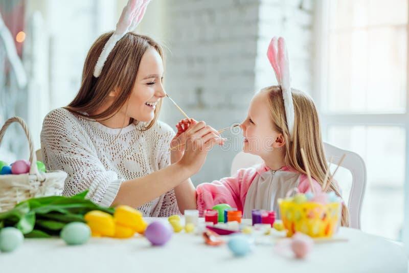Gör ett feriebarn Mamman och dottern förbereder sig för påsk tillsammans Mamman och dottern har en gyckel royaltyfri foto