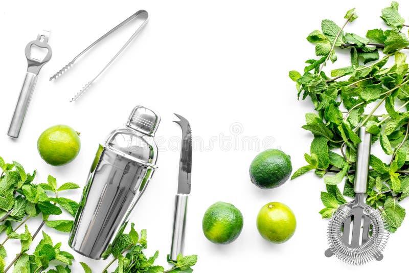 Gör mojitococtailen med limefrukt och pepparmint i shaker Vit copyspace för bästa sikt för bakgrund fotografering för bildbyråer