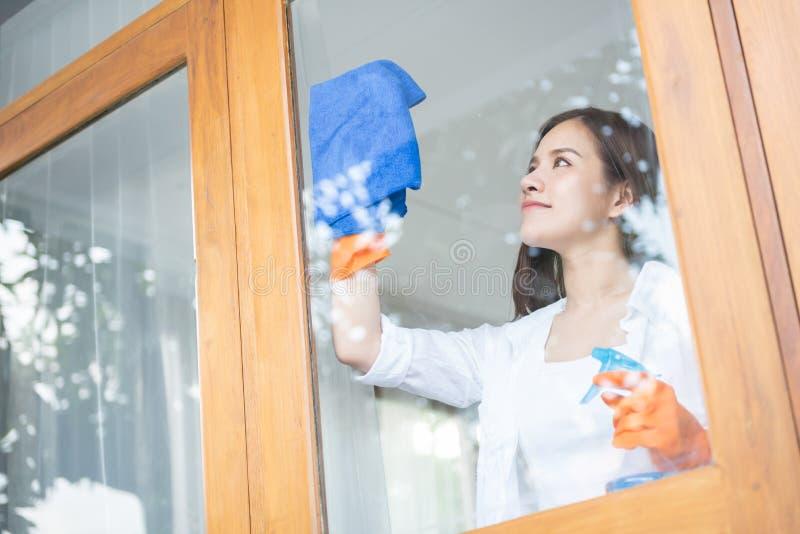 Gör orange handskar ren för asiatiska kvinnliga kläder hennes hus royaltyfria foton