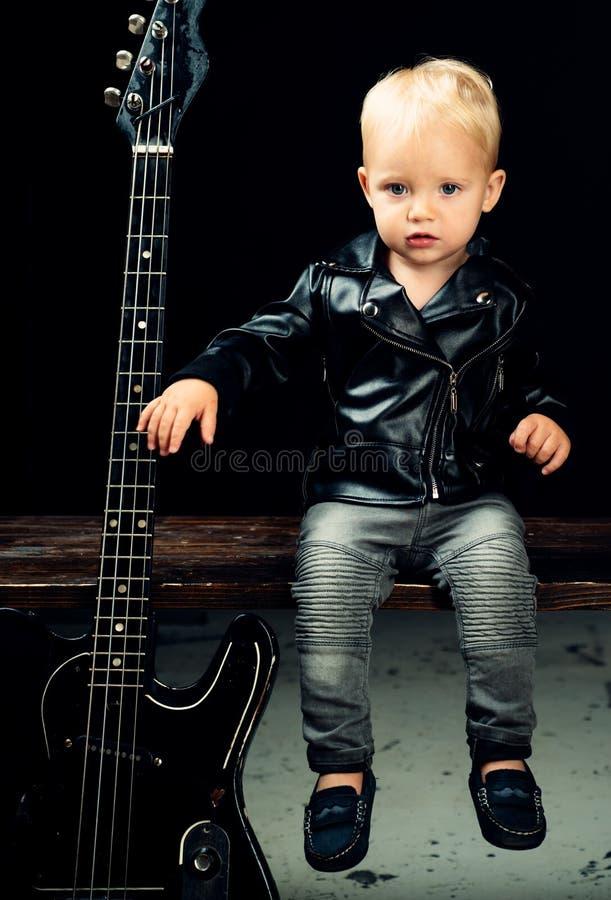 gör oväsen något Little rockstjärna Barnpojke med gitarren Liten gitarrist i vippaomslag Vagga stilbarnet vagga och royaltyfri fotografi
