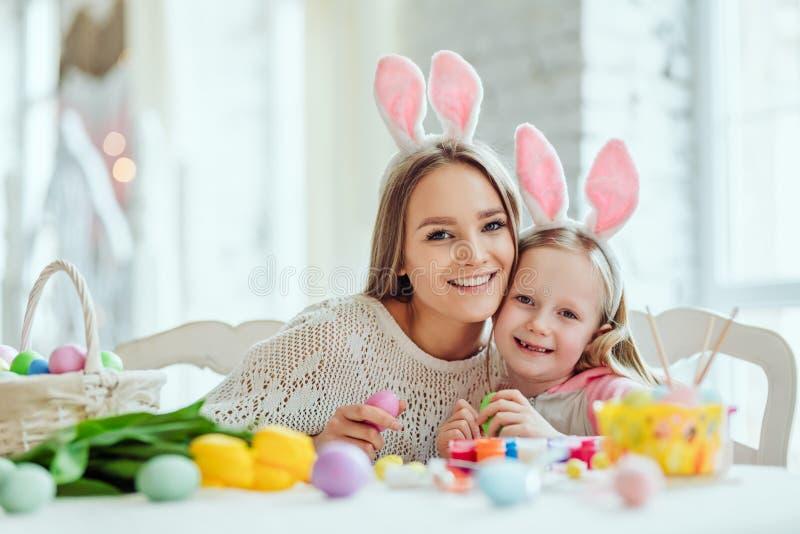 Gör påskförberedelsen rolig och söt Mamman och dottern förbereder sig för påsk tillsammans På tabellen är en korg med påskägg arkivbild