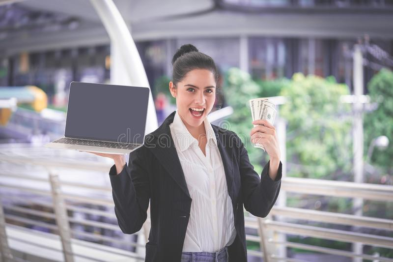Gör pengar online- på datoren med den rika kvinnan royaltyfri foto