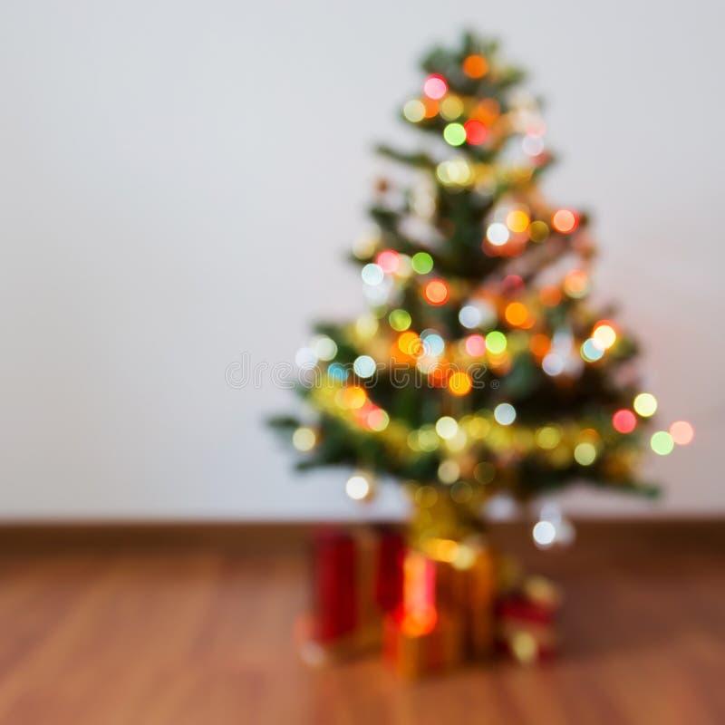 Gör suddig bakgrund, ljus beröm på julträd arkivbilder