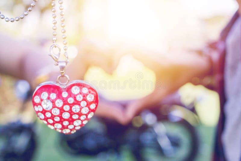 Gör suddig begreppet för dagen för ` s för valentin för solnedgången för halsbanddiamanten det hjärta formade ljusa arkivbild