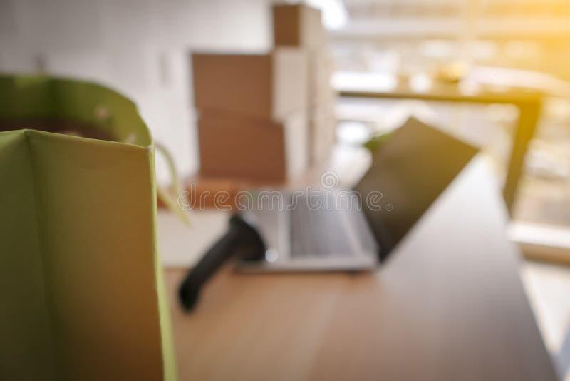 Gör suddig bilden av den gröna shoppa pappers- påsen med bärbara datorn royaltyfri foto