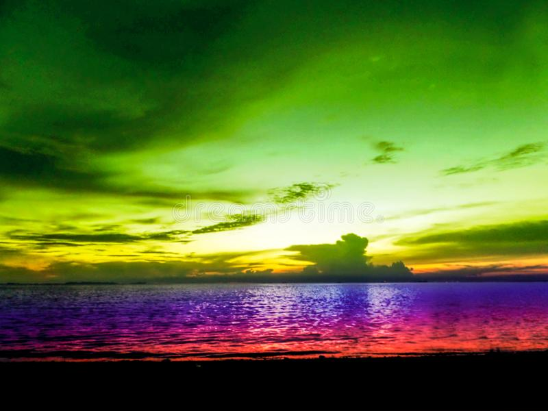 gör suddig färgrik himmel för den sista ljusa solnedgången och havet royaltyfria bilder