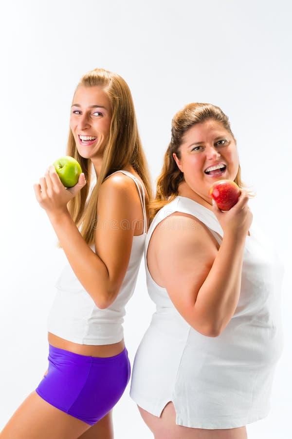 Gör tunnare och det hållande äpplet för den feta kvinnan i hand royaltyfri fotografi