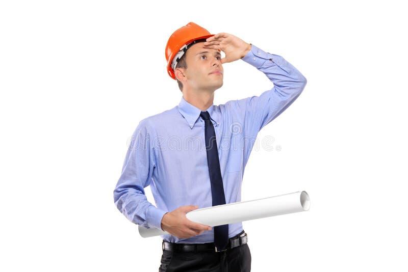 göra en skiss av konstruktionsholdingen som ser arbetaren royaltyfria bilder
