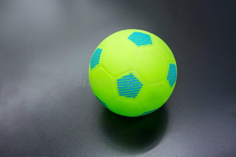 Göra grön och slösa fotbollbollen på svart matte golv royaltyfri bild