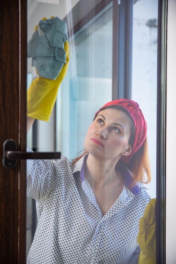 göra hushållsarbetekvinnan Hemmafru Portrait While Cleaning Foto till och med exponeringsglaset royaltyfria bilder