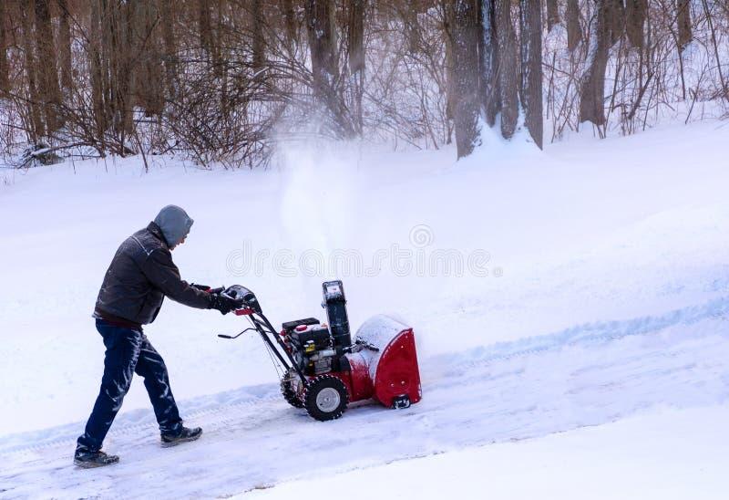 Göra klar snö från en drivway användande snowblower royaltyfria foton