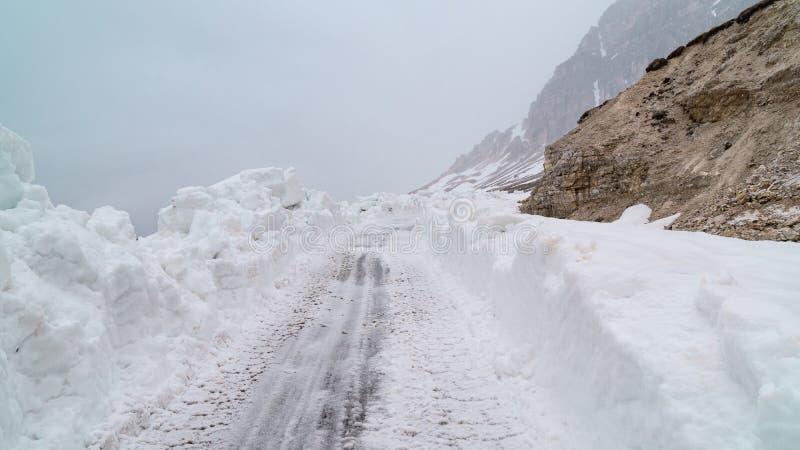 Göra klar vägen från insnöat bergen Dåligt väder i bergen blitzkrieg royaltyfri bild