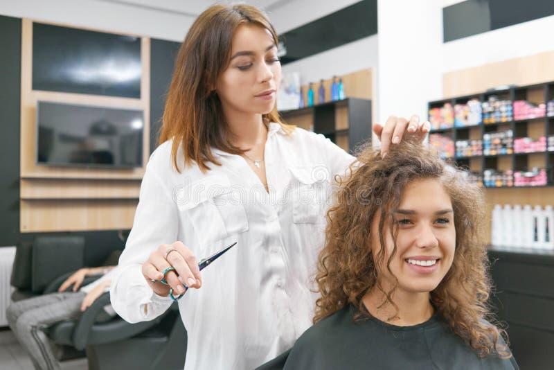 Göra nya hairdress för att le den lockiga kvinnliga klienten royaltyfri bild