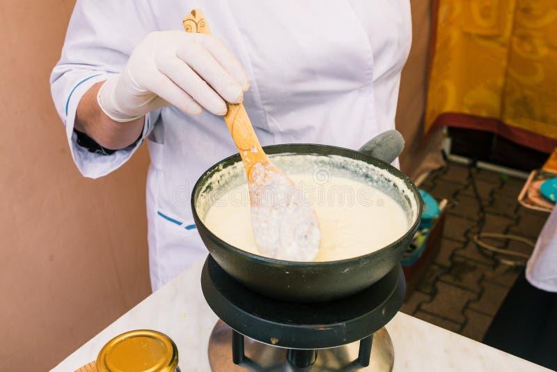Göra ost från mjölka hemma Kvinnlig sourdough för handuppståndelseost med en sked i en kastrull Teknologi av att laga mat ost arkivfoto