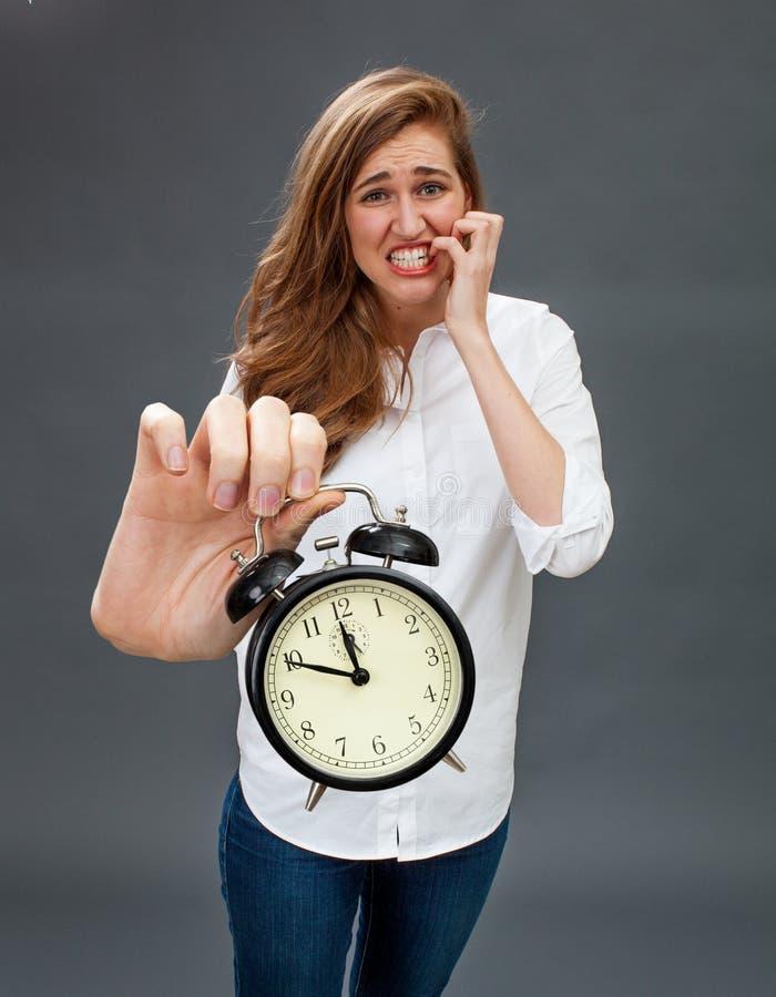 Göra panikslagen flicka som visar den pinsamma ringklockan för stramad åt tidledning royaltyfria foton