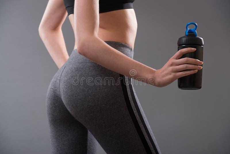 Göra perfekt form för den kvinnliga kroppen efter drinkar för kondition- och sportproteinmat royaltyfria foton