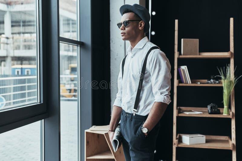 Göra perfekt stil Stilig ung man som ser bort och håller handen royaltyfria bilder