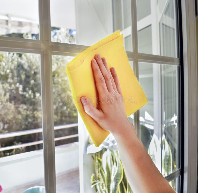 göra ren ett fönster med den gula torkduken arkivbilder