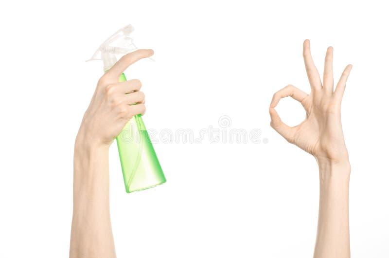 Göra ren hus- och rengöringsmedeltemat: mans hand som rymmer en grön sprejflaska för att göra ren isolerad på en vit bakgrund royaltyfri bild