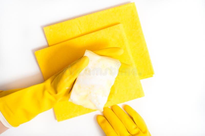G?ra ren hus- och sanitetsv?sen?mnet: Hand som rymmer en gul svamp v?t med skum som in isoleras p? en vit bakgrund royaltyfri bild