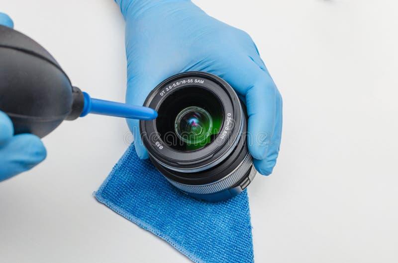 Göra ren linsen av en digital kamera från damm genom att använda en blåsare Yrkesmässig service för digital kamera royaltyfri fotografi