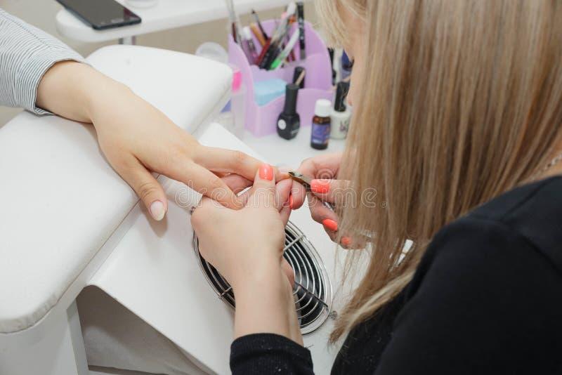 Göra ren och arrangera i rak linje nagelbandet med kirurgisk tång i rota av spikar arkivbild