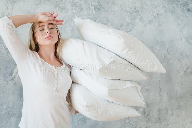 Göra sängmorgonsysslor trötta kvinnakuddar fotografering för bildbyråer