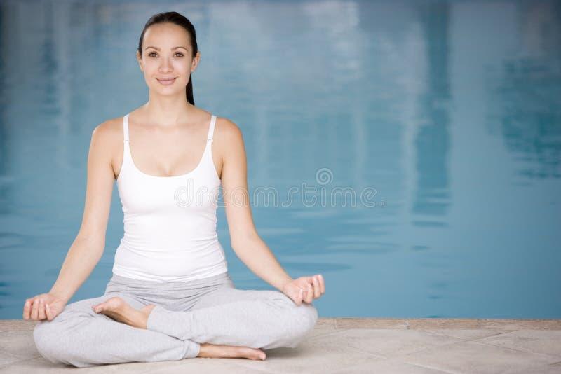 göra sittande kvinnayoga för poolside royaltyfri fotografi